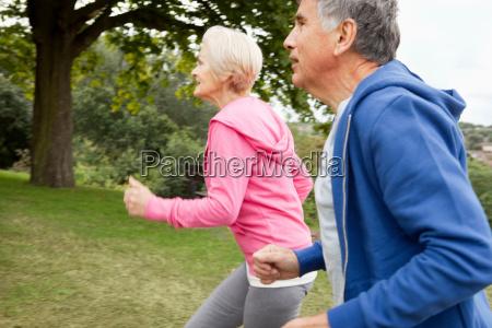 mature couple jogging in park