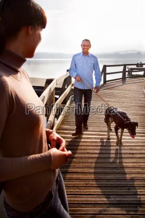 couple walking dog on pier