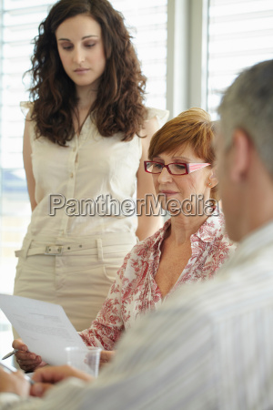 older business woman reading document