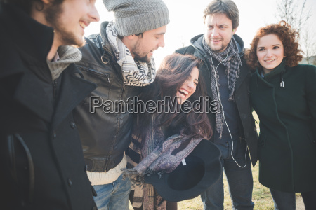 five young adult friends laughing together
