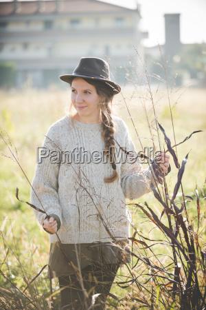 mloda kobieta w kapeluszu dotykajac roslin
