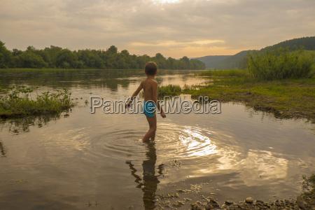 young boy paddling in lake at