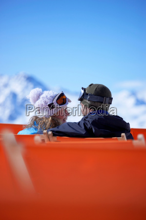 couple sitting close in chair lift