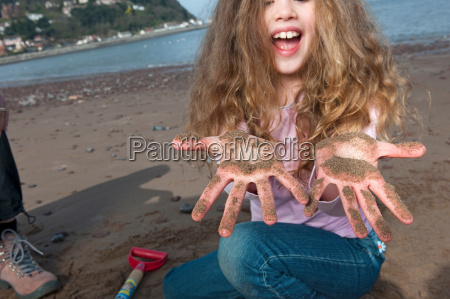 child with sandy hands on beach