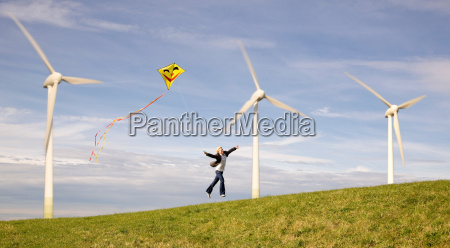 man jumping with kite at wind
