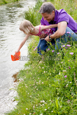 father and daughter playing on creek