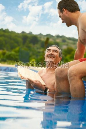 older man reading news in swimming