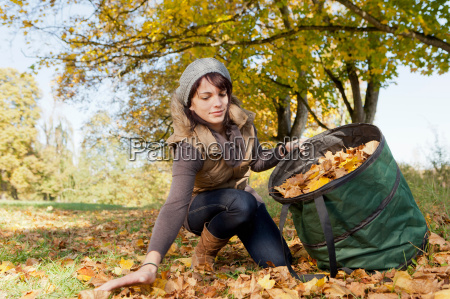 woman gathering fall leaves in park