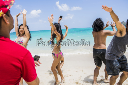 young adult friends dancing on lanikai