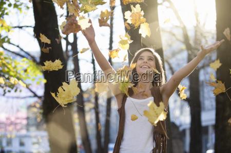 polowa doroslych kobieta rzuca lisci jesienia