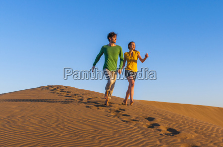 romantic mid adult couple running on