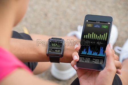 running kobieta z telefonem komorkowym podlaczony