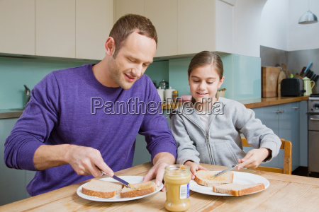 father and daughter spreading peanut butter