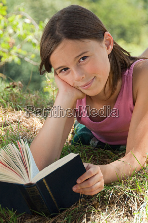 girls lying on front with book