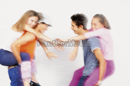 teenage boys and girls playing piggyback
