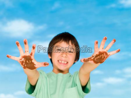 a boy with chocolate covered hands