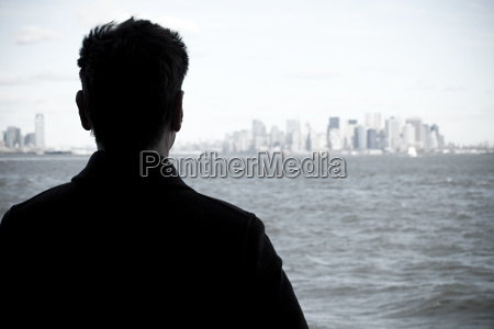 man looking over river to manhattan