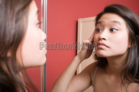 young woman looking at reflection in