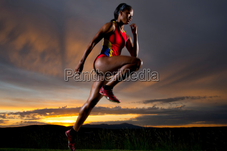 athlete in mid air against sunset