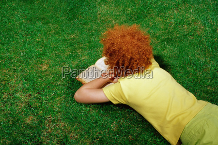 girl lying on the grass reading