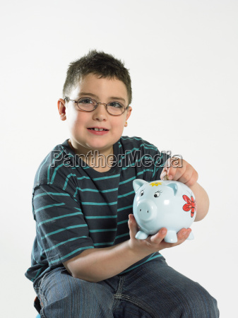 boy putting coin in piggy bank