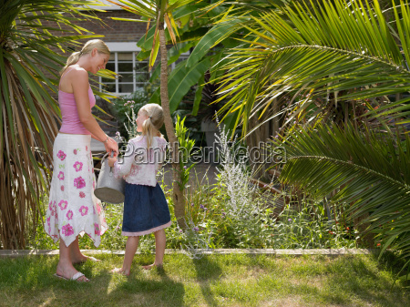 mother and daughter watering garden