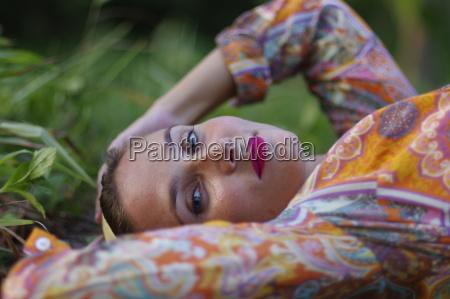 potrait mlodej kobiety lezacej na trawie