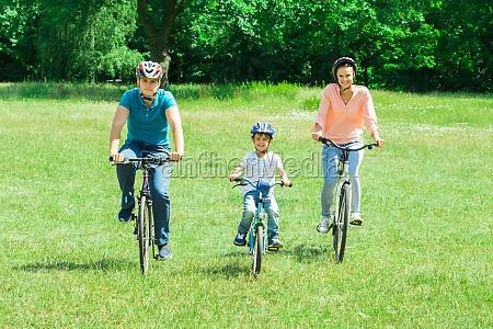 chlopiec z rodzicem jazda na rowerze