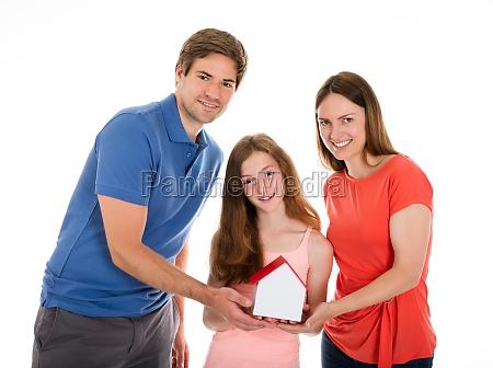 smiling family holding house model