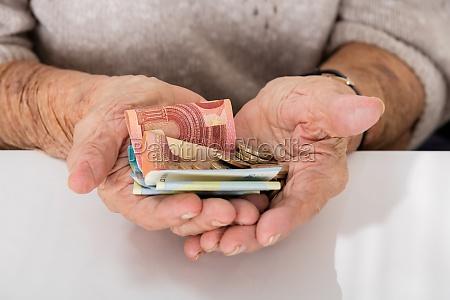 starsza kobieta pokazujac pieniadze na palme