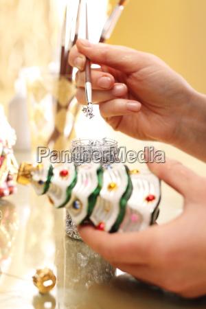 decorating christmas baubles the woman paints