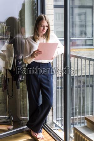 woman standing at open glass door