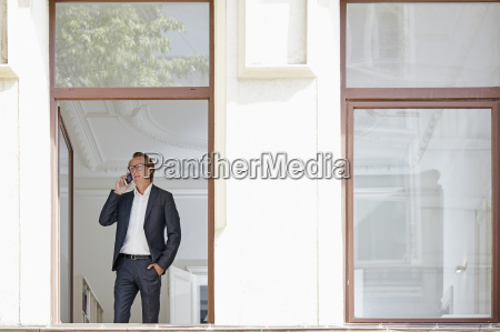businessman telephoning with smartphone while looking