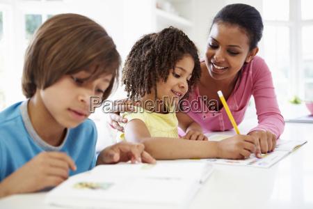 matka pomaga dzieciom z pracy domowej