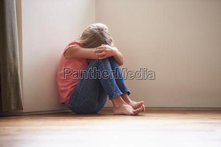 unhappy dziecko siedzi na podlodze w