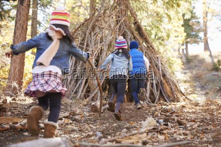 troje dzieci bawic sie poza schronienie