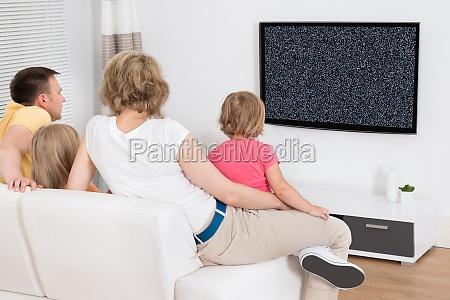 mloda rodzina oglada tv wpolnie