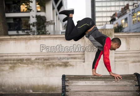 young man jumping over park bench