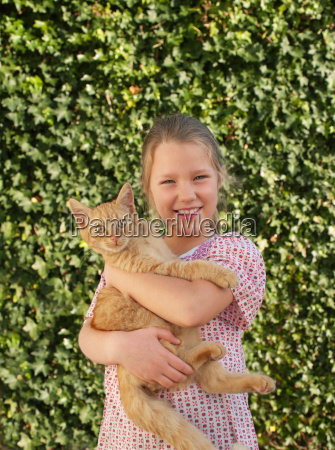 young girl holding pet cat smiling