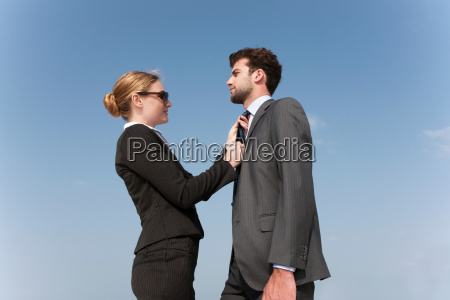 businesswoman adjusting colleagues tie