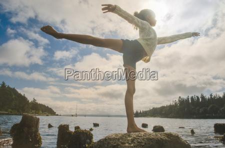 ballet dancing girl poised on rock