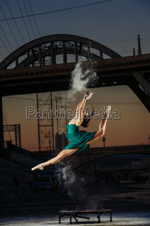 female dancer leaping whilst releasing powder