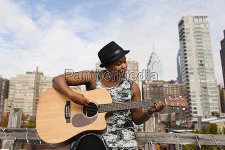 mature woman playing guitar in front