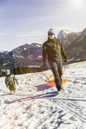 man pulling sled on snow achenkirch