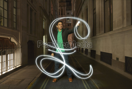 businessman light painting glowing pound sign