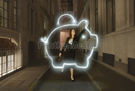 businesswoman light painting glowing piggy bank