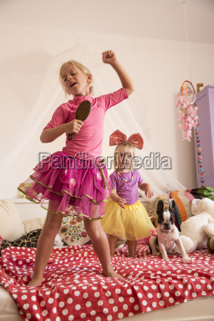girl and toddler sister dancing and