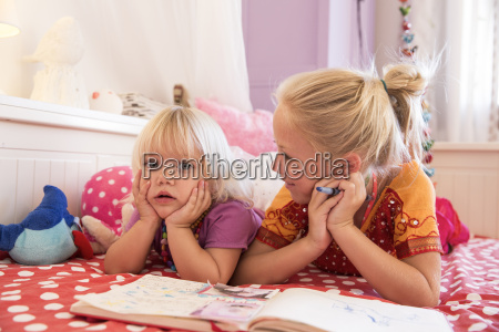 girl and toddler sister on bed