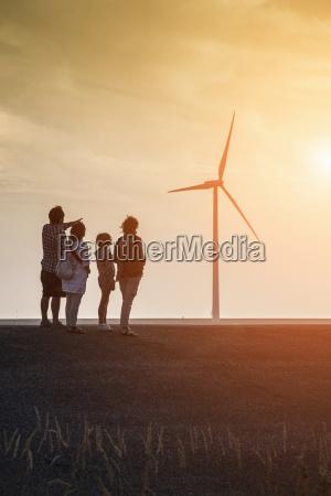 grupa rodzina patrzac na turbiny wiatrowe