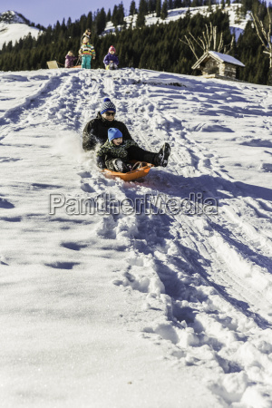 father and son riding sled down